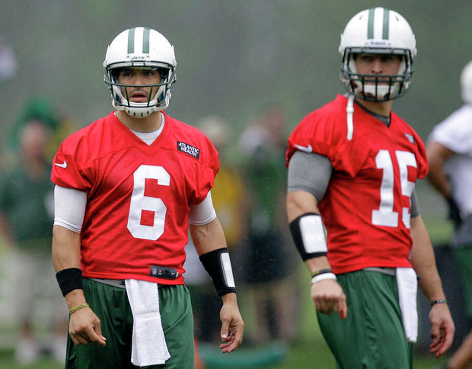 New York Jets quarterbacks Mark Sanchez, left, and Tim Tebow look on during NFL football practice, Thursday, May 24, 2012, in Florham Park, N.J. (AP Photo/Julio Cortez) / AP