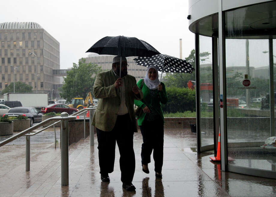 Mohamed El-Filali, left, of Paterson, N.J. hurries in the rain with Nadia Kahf, attorney with the Council on American-Islamic Relations in New Jersey as they head to a meeting with New Jersey Attorney General Jeffrey S. Chiesa and Muslim leaders in Trenton, N.J., Thursday, May 24, 2012 . Following a three-month review, Gov. Chris Christie's administration said Thursday that New York City police did not violate New Jersey laws when they conducted surveillance of Muslim businesses, mosques and student groups, rejecting demands by Muslim leaders for a formal investigation and a clampdown on cross-border police operations. (AP Photo/Mel Evans)s / AP