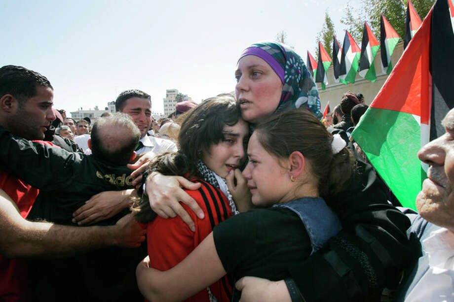 A released Palestinian prisoner embraces her daughters in the West Bank city of Ramallah, Tuesday, Oct. 18, 2011. Hamas agreed to release Israeli soldier Galit Schalit in exchange for 1,027 Palestinian prisoners, many of them serving life sentences for deadly attacks on Israelis. The arrivals of the prisoners set off ecstatic celebrations in the West Bank and Gaza Strip, where large crowds and dignitaries greeted them. (AP Photo/Nasser Ishtayeh) / AP