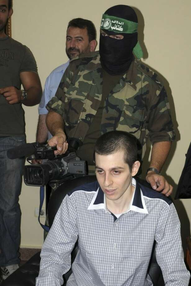A Hamas cameraman stands behind released Israeli soldier Gilad Schalit on the Egyptian side of the Rafah border crossing, Monday, Oct. 18, 2011. Looking dazed, a thin and pale, Gilad Schalit emerged from a pickup truck Tuesday under the escort of his Hamas captors and the Egyptian mediators who helped arrange the Israeli tank crewman's release after more than five years in captivity. (AP Photo/Khalid Farid)