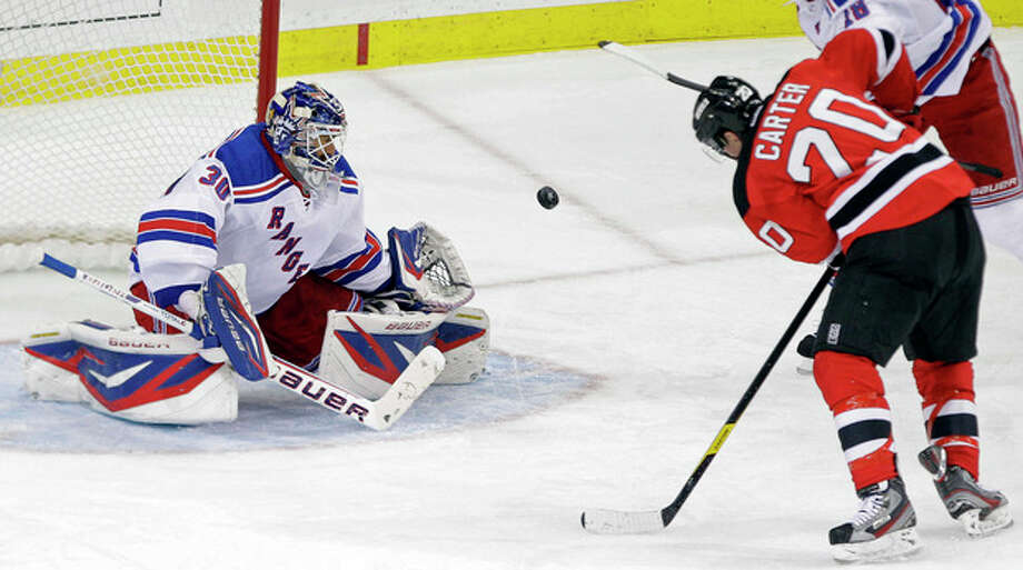 New York Rangers goalie Henrik Lundqvist (30), of Sweden, stops a shot on the goal by New Jersey Devils' Ryan Carter (20) during the third period of game 3 of an NHL hockey Stanley Cup Eastern Conference final playoff series Saturday, May 19, 2012, in Newark, N.J. (AP Photo/Frank Franklin II) / AP