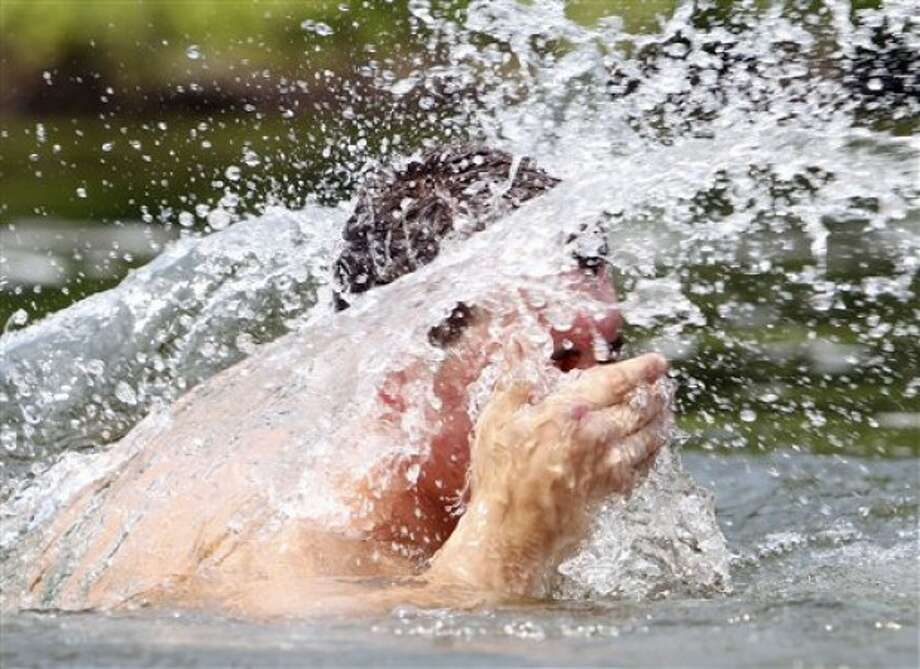 David Smith of Philmont, N.Y., cools off while swimming in the Kinderhook Creek in Stuyvesant Falls, N.Y., on Wednesday, June 8, 2011. The National Weather Service says temperatures will reach the low to mid-90s, with uncomfortable humidity, in much of upstate as some East Coast metropolitan areas are expected to see temperatures approaching 100 degrees. (AP Photo/Mike Groll)