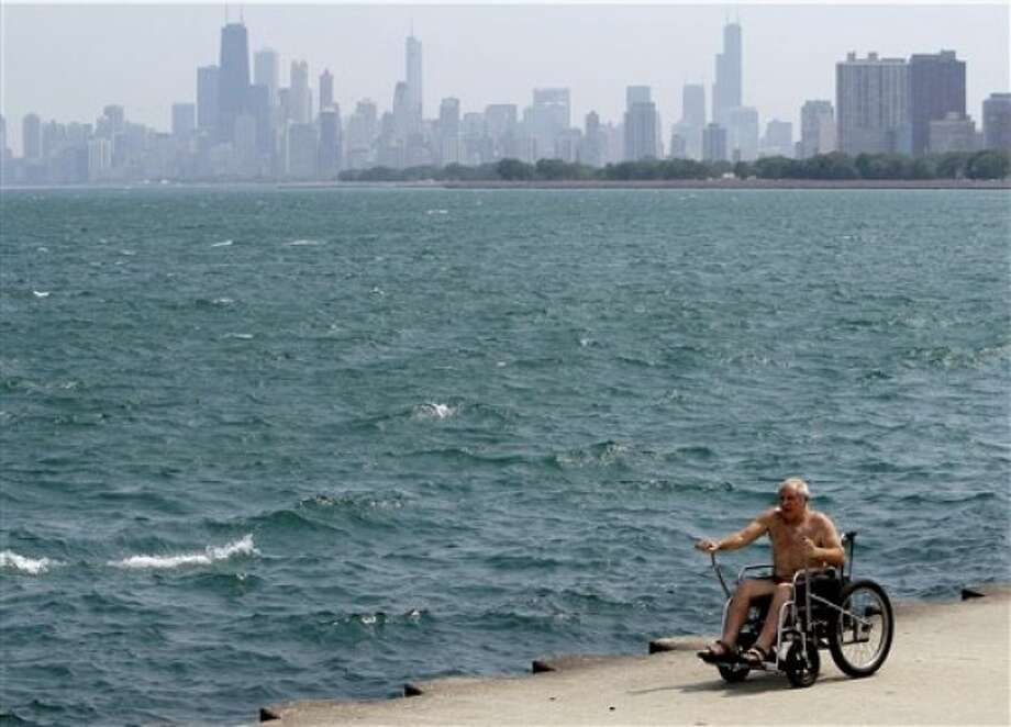 A man rides his wheelchair during hot weather at Montrose beach in Chicago, June 8, 2011. Temperatures peaked Wednesday within a few degrees of the 97-degree 1933 record. (AP Photo/Nam Y. Huh)