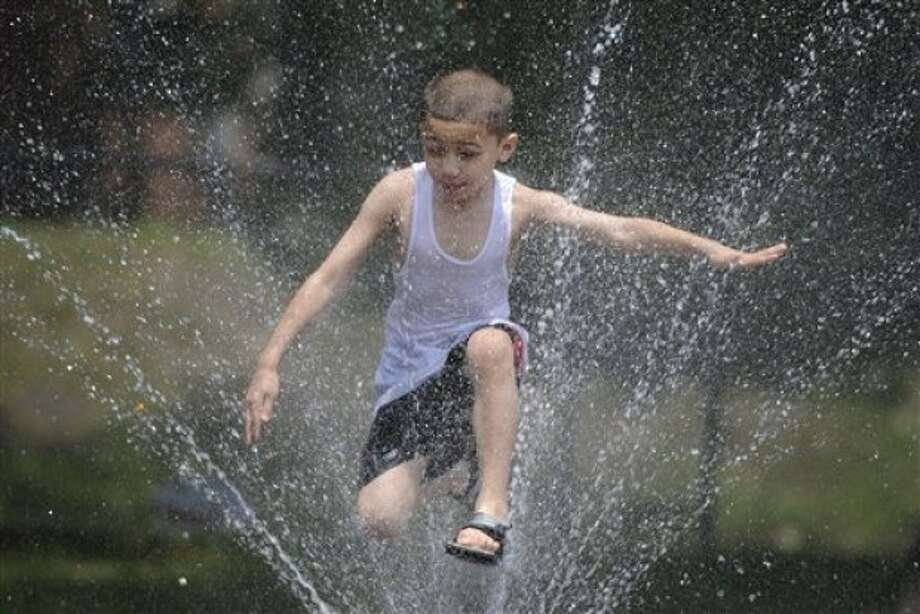 Noah DeLaCruz of Hartford cools off in a fountain in Hartford, Conn., Wednesday, June 8, 2011. (AP Photo/Jessica Hill)