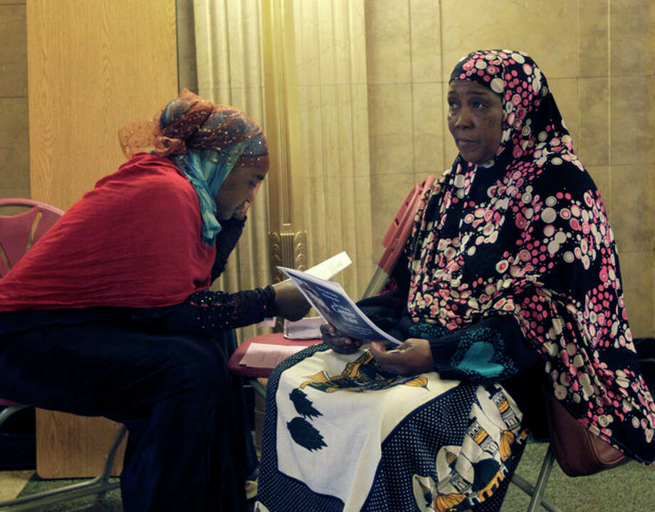 In an April 12, 2012 photo, Mariyamo Bakar, left, and Hawa Mugolo fill out job applications during a career fair in Buffalo, N.Y. The number of people seeking unemployment aid changed little last week, a sign that hiring may continue at a modest pace. The Labor Department says that weekly unemployment benefit applications dipped 2,000 to a seasonally adjusted 370,000. Applications have fluctuated around that level for the past month. The four-week average, a less volatile measure, is also 370,000. Applications spiked in April to 392,000, a five-month high, then fell back. They have leveled off in May. (AP Photo/David Duprey) / AP