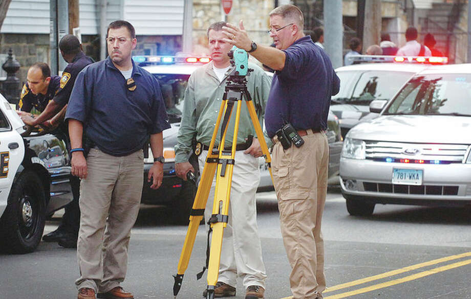 Hour Photo/ Alex von Kleydorff. Norwalk Police detectives and Crime Scene Investigaors set up in front of 119 So. Main St. after a man was shot Wednesday late afternoon. / 2012 The Hour Newspapers