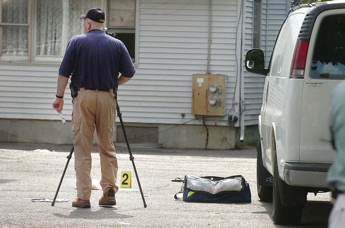 Hour Photo/ Alex von Kleydorff. Norwalk Police crime scene investigator Art Weisgerber takes some photos at a shooting late Wednesday Afternoon at 119 South Main St.