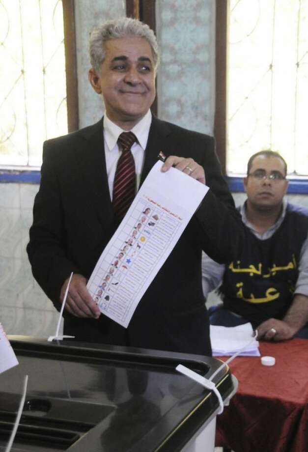 Egyptian presidential candidate, Hamdeen Sabahi shows the ballot paper after voting inside a polling station in Cairo, Egypt, Wednesday, May 23, 2012. More than 15 months after autocratic leader Hosni Mubarak's ouster, Egyptians streamed to polling stations Wednesday to freely choose a president for the first time in generations. (AP Photo/Ahmed Hammad)