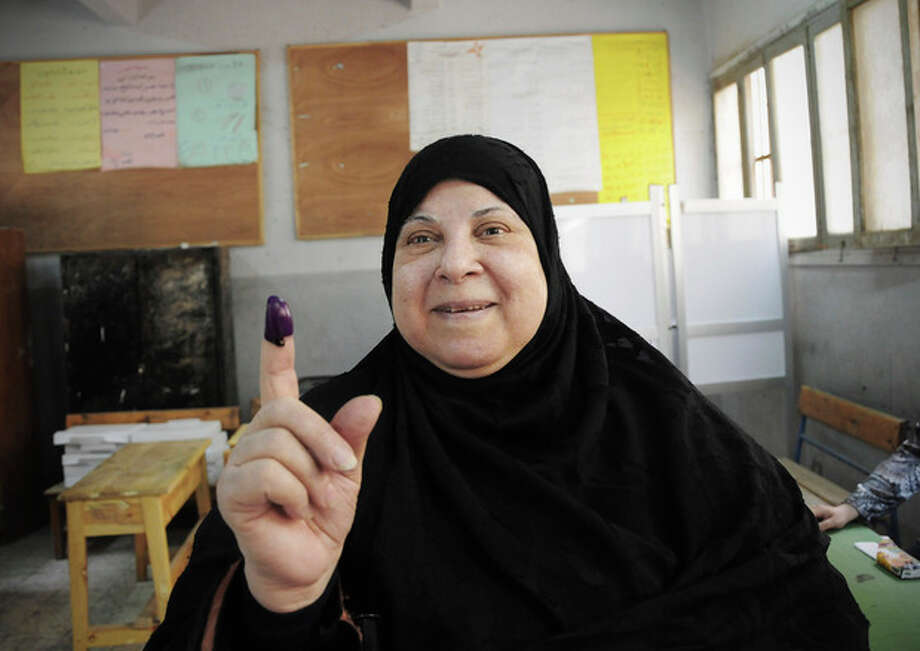 An Egyptian woman shows her inked finger after casting her vote inside a polling station, in Giza, Egypt, Wednesday, May 23, 2012. More than 15 months after autocratic leader Hosni Mubarak's ouster, Egyptians streamed to polling stations Wednesday to freely choose a president for the first time in generations. (AP Photo/Mohammed Asad) / AP