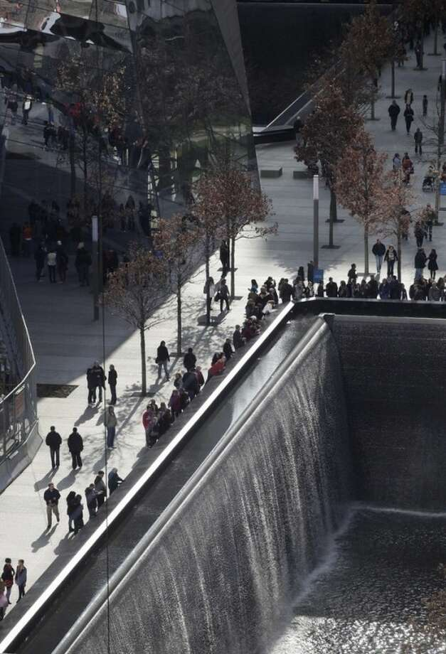 Visitors to the National September 11 Memorial and Museum circle one of two reflecting pools, on Monday, Nov. 21, 2011, in New York. The opening of the museum at the World Trade Center, planned for Sept. 11, 2012, will be delayed by disputes over redevelopment costs, a person familiar with the construction project said Monday. The memorial opened in September on the 10th anniversary of the 2001 attacks. (AP Photo/Mark Lennihan)