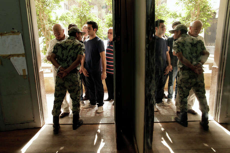 An Egyptian Army soldier stands guard inside a polling station as men wait to cast their votes in the country's presidential election on Wednesday, May 23, 2012 in the Zamalek neighborhood of Cairo, Egypt. Determined to end decades of authoritarian rule, millions of Egyptians on Wednesday waited patiently in long lines outside polling stations across the nation to freely chose their first president since last year's ouster of longtime ruler and close U.S. ally Hosni Mubarak. (AP Photo/Maya Alleruzzo) / Copyright 2012 The Associated Press. All rights reserved. This material may not be published, broadcast, rewritten or redistributed.
