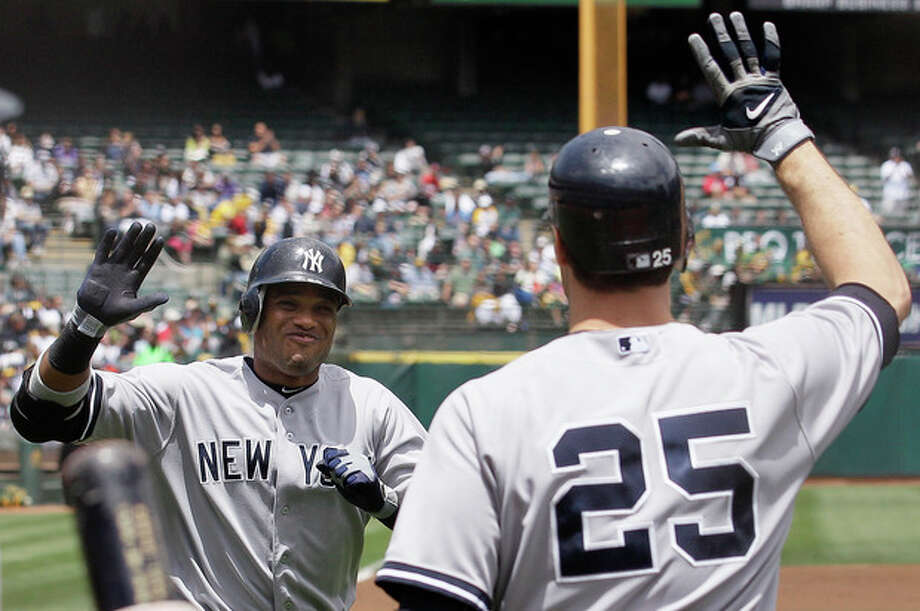 New York Yankees' Robinson Cano, left, celebrates with Mark Teixeira after hitting a solo home run off Oakland Athletics pitcher Bartolo Colon during the second inning of a baseball game in Oakland, Calif., Saturday, May 26, 2012. (AP Photo/Jeff Chiu) / AP