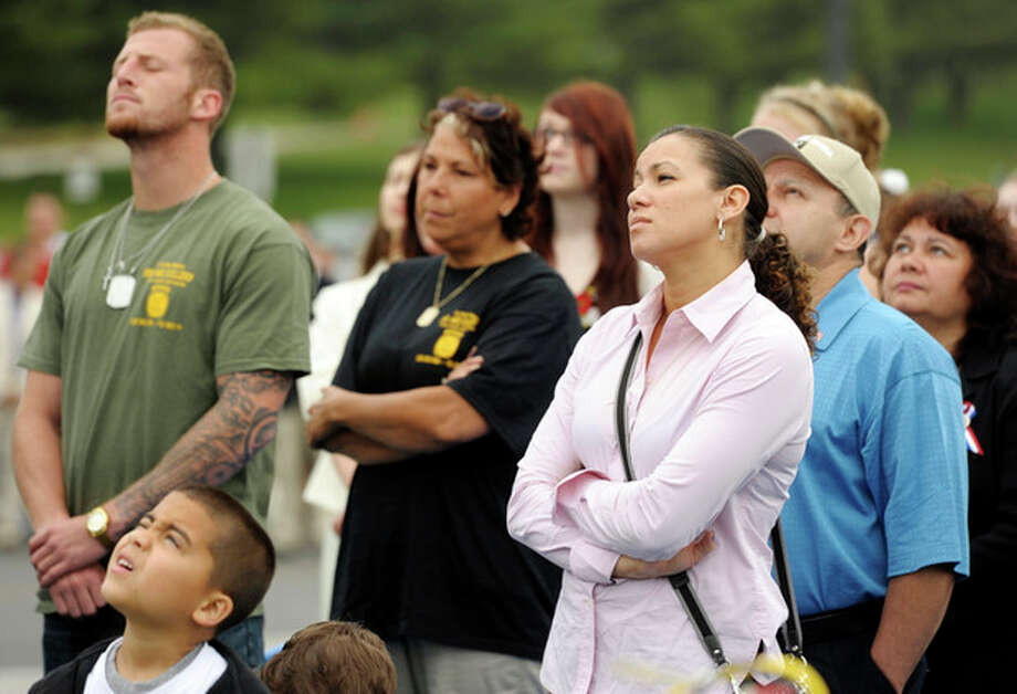 Miriam Rivera, sister of fallen Connecticut Army National Guard Sgt. Edwin Rivera, stands with her parents, Ceferino and Gladys and Edwin's son Lorenzo, 6, and Jacob and Robin Cullers, brother and mother of fallen U.S. Army Staff Sgt. Ari Cullers, as the flag is raised by an honor guard of students at Waterford, Conn., High School students who are either enlisted in the military or college ROTC programs during a Memorial Day ceremony Friday, May 25, 2012 to remember four alumni of the school killed in action as members of the U.S. Military. The ceremony honored Arnold Holm (Vietnam), Kemaphoom Chanawongse (Iraq) and Rivera and Cullers (Afghanistan). (AP Photo/The Day, Sean D. Elliot) / 2012 The Day Publishing Company