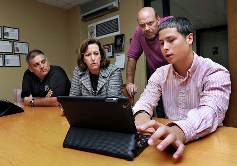 ADVANCE FOR WEEKEND EDITIONS MAY 26-27 - In this May 22, 2012 photo, former student Ryan Nolan, right, discusses the app he is designing as part of the new iPad initiative with, from left, principal Joseph Carmen, school president Kathleen Casey, and tech co-ordinator Dave Cirella, at Immaculate High School, in Danbury, Conn. (AP Photo/Carol Kaliff, The News-Times) MANDATORY CREDIT / The News-Times
