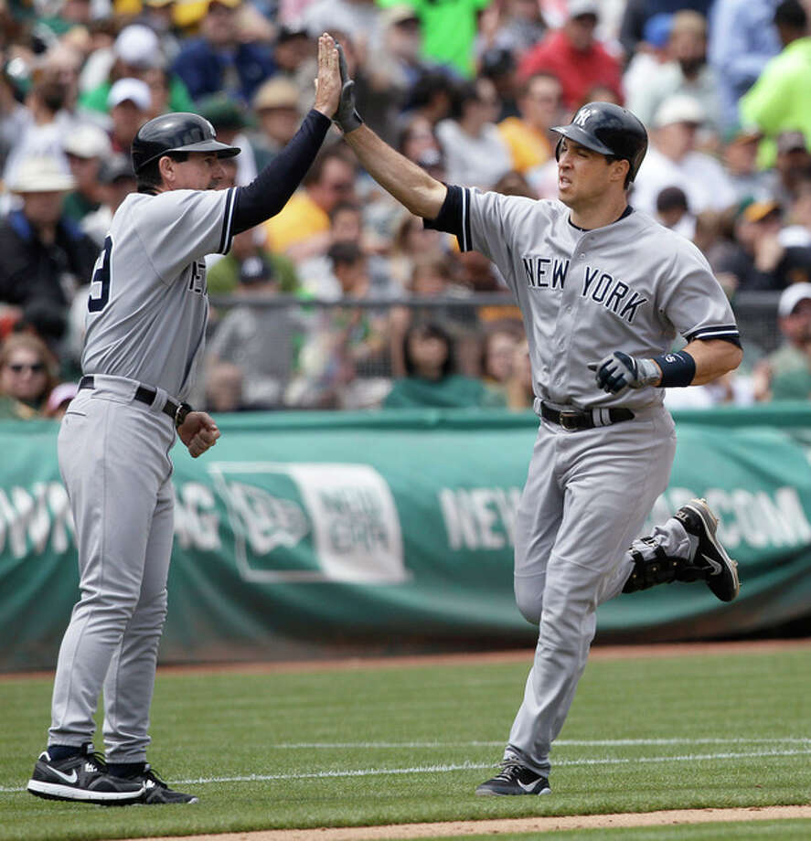 New York Yankees' Mark Teixeira, right, celebrates with third base coach Rob Thomson after hitting a solo home run off of Oakland Athletics pitcher Bartolo Colon during the fourth inning of a baseball game in Oakland, Calif., Saturday, May 26, 2012. (AP Photo/Jeff Chiu) / AP