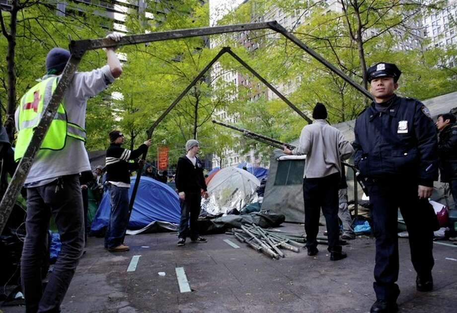 A police officer walks by as Occupy Wall Street protesters erect a large military-style tent in Zuccotti Park in New York, Monday, Nov. 7, 2011. (AP Photo/Seth Wenig) / AP