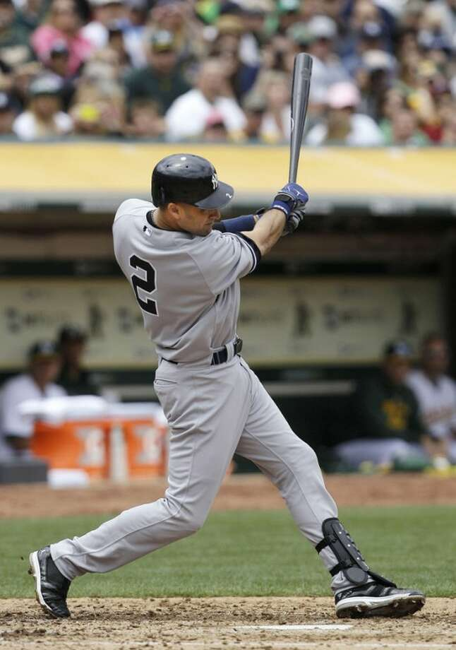 New York Yankees' Derek Jeter swings on a single off Oakland Athletics pitcher Bartolo Colon to score Eric Chavez during the third inning of a baseball game in Oakland, Calif., Saturday, May 26, 2012. (AP Photo/Jeff Chiu)