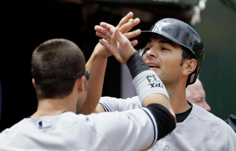 New York Yankees' Eric Chavez, right, celebrates with Nick Swisher after scoring on Derek Jeter's base hit against the Oakland Athletics during the third inning of a baseball game in Oakland, Calif., Saturday, May 26, 2012. (AP Photo/Jeff Chiu) / AP