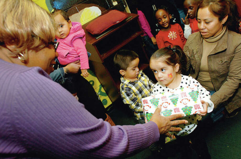 Hour photos / Erik Trautmann Bethany Ortega recieves a Christmas gift from Veronica Richards at the Community Day of Sharing at The George Washington Carver Community Center with her grandmother Clementina Ortega Saturday. / (C)2011, The Hour Newspapers, all rights reserved