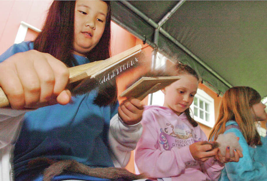 CIder Mill Elementary School 4th graders Sarah Bell and Megan MacNamara learn how to comb wool during the Wilton Historical Society's history immersion program where students recieve hands-on learning on how people lived in colonial times.Hour photo / Erik Trautmann / (C)2012, The Hour Newspapers, all rights reserved