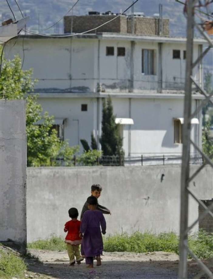 """FILE - In this May 8, 2011 file photo, Pakistani children walk past the house of former al-Qaida leader Osama bin Laden in Abbottabad, Pakistan. Osama bin Laden''s Yemeni wife once dismissed the terror leader''s offer to return to the safety of her home, saying she wanted to stay and be """"martyred"""" alongside her husband, her family says. In interviews with The Associated Press, Amal al-Sada''s relatives paint a portrait of an ambitious, resolute and conservative young woman told friends and family she hoped to """"go down in history"""" after her marriage to the world''s most wanted man. (AP Photo/Anjum Naveed, File)"""