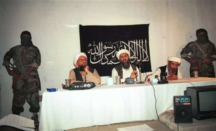 FILE - This 1998 file photo showing exiled al Qaida leader Osama bin Laden, center, the prime suspect behind the Sept. 11, 2001 terrorist attacks in the United States, flanked by his aides and armed bodyguards in a meeting at an undisclosed location in Afghanistan, according to the source. In the background is a banner with a verse from the Quran, Islam''s holy book. This photo was offered to the Associated Press on Sept. 22, 2001 from a Pakistani photographer who wants to remain anonymous. For a man on the run, Osama bin laden seemed to do very little running. Instead, he chose to spend long stretches _ possibly years _ in one place and often in the company of his family. (AP Photo, File)