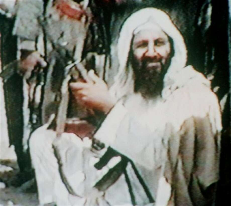 FILE - This image made from television shows Osama bin Laden holding an AK47 automatic rifle in an undated recruitment video tape for his organization, as viewed by The Associated Press in Kuwait City on Tuesday, June 19, 2001. The Associated Press viewed the tape at the offices of Al-Rai Al-Amm, a Kuwaiti daily newspaper that published a story about the video Tuesday. The newspaper would not say how or where it acquired the video. For a man on the run, Osama bin laden seemed to do very little running. Instead, he chose to spend long stretches _ possibly years _ in one place and often in the company of his family. (AP Photo, File)