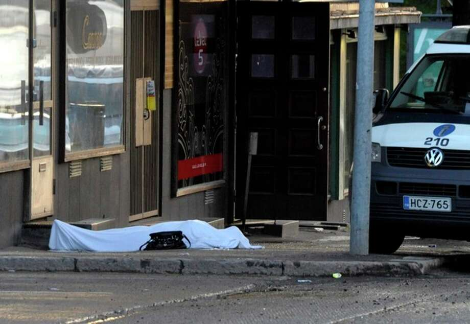 A body covered with a sheet lies on the street in Hyvinkaa, Finland, Saturday May 26, 2012. A gunman in southern Finland has killed one person and wounded eight others in what appeared to be a random shooting, police said Saturday. (AP Photo/Lehtikuva/Sari Gustafsson) FINLAND OUT / Lehtikuva