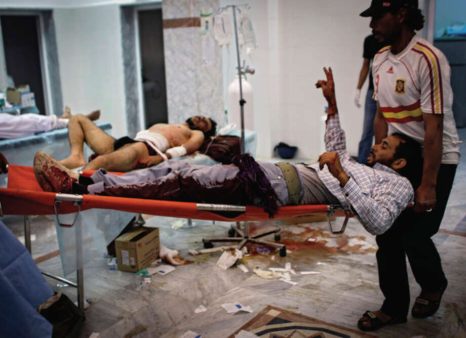 Volunteers carry a wounded rebel fighter in the Abu-Rafat hospital on the outskirts of Zawiya, LIbya, Sunday, Aug. 21, 2011. Libyan rebels said they were less than 20 miles (30 kilometers) from Moammar Gadhafi's main stronghold of Tripoli on Sunday, a day after opposition fighters launched their first attack on the capital itself. Fighters said a 600-strong rebel force that set out from Zawiya has reached the outskirts of the village of Jedaim and was coming under heavy fire from regime forces on the eastern side of the town. (AP Photo/Sergey Ponomarev) / AP