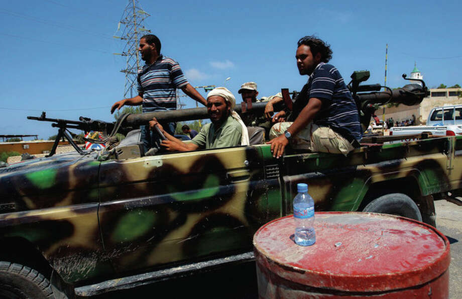 RETRANSMISSION FOR IMPROVED QUALITY Rebel fighters speed towards the frontllne fighting in the village of Mayah, some 30 kilometers west from Tripoli, LIbya, Sunday, Aug. 21, 2011. (AP Photo/Sergey Ponomarev) / AP