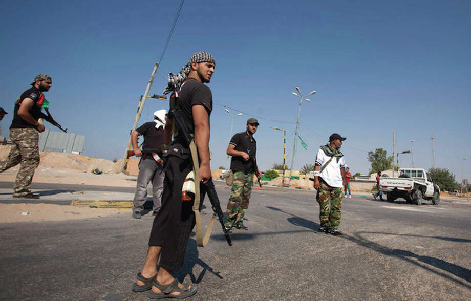 Libyan rebel fighters seen at the checkpoint outside Zawiya, Libya, Saturday, Aug. 20, 2011. Libyan rebels expelled government forces from the strategic western city of Zawiya on Saturday, a major victory for the opposition in their march on Moammar Kadafi's stronghold of Tripoli. (AP Photo/Giulio Petrocco) / AP