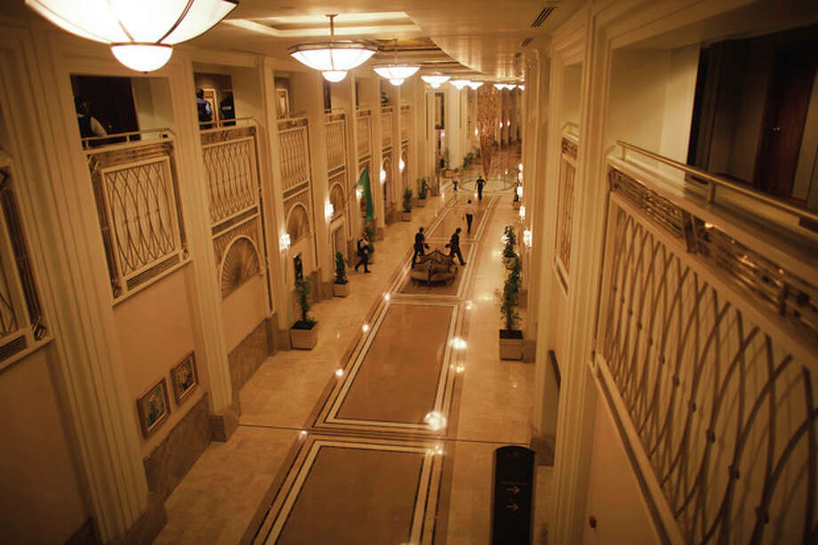 People prepare as they walk through the main lobby of the Rixos hotel in Tripoli, Libya, Sunday, Aug. 21, 2011. Gunfire has erupted all around the hotel which houses the state TV, the Libyan government spokesman and the international media.(AP Photo/Dario Lopez-Mills) / AP