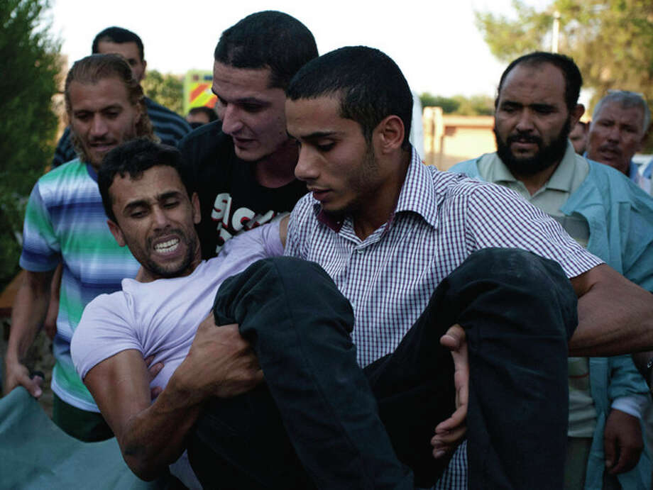 In this Friday, Aug. 19, 2011 photo, people help a wounded rebel fighter to a stretcher at a field hospital on the south outskirts of Zawiya, Libya. Libyan rebels expelled government forces from the strategic western city of Zawiya on Saturday, a major victory for the opposition in their march on Moammar Kadafi's stronghold of Tripoli. (AP Photo/Giulio Petrocco) / AP