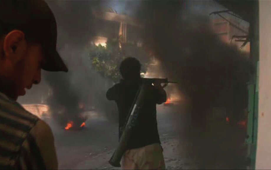 In this image from video a rebel fighter fires a weapon through tire smoke on a street in Zawiya, Libya Friday Aug.19 2011 as they battled for control of the strategic central square against forces loyal to Moammar Gadhafi. Rebel forces were reported to have expelled government forces from Zawiya, a coastal city just 30 miles (50 kilometers) west of Tripoli, on Saturday Aug. 20. They also claim to have captured two more towns - Zlitan in the west and Brega in the east. The momentum in the six-month-old Libyan civil war now appears to have firmly swung in the rebels favor after months of near deadlock. (AP Photo/Sky via APTN) / Sky via APTN