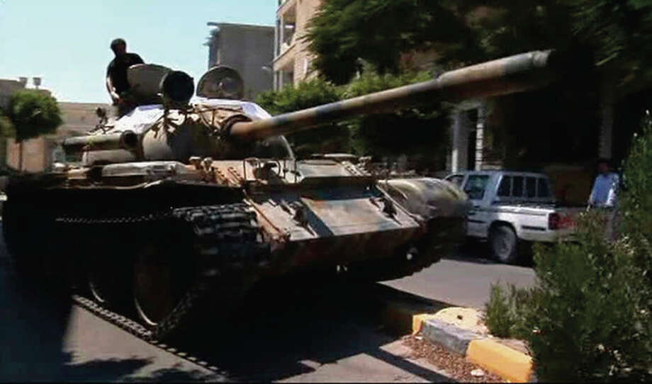 In this image from video a captured tank bearing a rebel flag maneuvers on a street in Zawiya, Libya Friday Aug.19 2011 as they battled for control of the strategic central square against forces loyal to Moammar Gadhafi. Rebel forces were reported to have expelled government forces from Zawiya, a coastal city just 30 miles (50 kilometers) west of Tripoli, on Saturday Aug. 20. They also claim to have captured two more towns - Zlitan in the west and Brega in the east. The momentum in the six-month-old Libyan civil war now appears to have firmly swung in the rebels favor after months of near deadlock. (AP Photo/Sky via APTN) / Sky via APTN