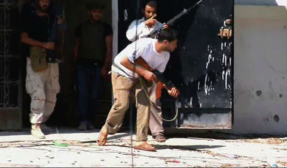 In this image from video a rebel fighter runs to take a position on a street in Zawiya, Libya Friday Aug.19 2011 as they battled for control of the strategic central square against forces loyal to Moammar Gadhafi. Rebel forces were reported to have expelled government forces from Zawiya, a coastal city just 30 miles (50 kilometers) west of Tripoli, on Saturday Aug. 20. They also claim to have captured two more towns - Zlitan in the west and Brega in the east. The momentum in the six-month-old Libyan civil war now appears to have firmly swung in the rebels favor after months of near deadlock. (AP Photo/Sky via APTN) / Sky via APTN