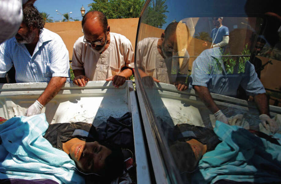 Medics check the body of killed a pro-Gadhafi fighter in the Abu-Rafat hospital on the outskirts of Zawiya, LIbya, Sunday, Aug. 21, 2011. Libyan rebels said they were less than 20 miles (30 kilometers) from Moammar Gadhafi's main stronghold of Tripoli on Sunday, a day after opposition fighters launched their first attack on the capital itself. Fighters said a 600-strong rebel force that set out from Zawiya has reached the outskirts of the village of Jedaim and was coming under heavy fire from regime forces on the eastern side of the town. (AP Photo/Sergey Ponomarev) / AP