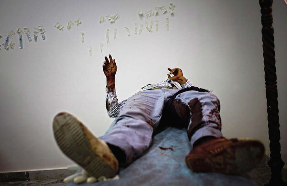 A wounded rebel fighter flashes a V-sign in the Abu-Rafat hospital on the outskirts of Zawiya, LIbya, Sunday, Aug. 21, 2011. Libyan rebels said they were less than 20 miles (30 kilometers) from Moammar Gadhafi's main stronghold of Tripoli on Sunday, a day after opposition fighters launched their first attack on the capital itself. Fighters said a 600-strong rebel force that set out from Zawiya has reached the outskirts of the village of Jedaim and was coming under heavy fire from regime forces on the eastern side of the town. (AP Photo/Sergey Ponomarev) / AP