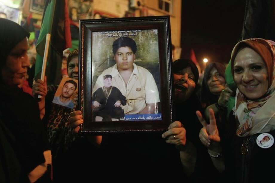 Women hold a picture of a boy allegedly killed during a bombing attack in the city of Brega as people celebrate the recent news of uprising in Tripoli against Moammar Gadhafi's regime at the rebel-held town of Benghazi, Libya, early Sunday, Aug. 21, 2011. Libyan rebels said they launched their first attack on Tripoli in coordination with NATO late Saturday, and Associated Press reporters heard unusually heavy gunfire and explosions in the capital. The fighting erupted just hours after opposition fighters captured the key city of Zawiya nearby. (AP Photo/Alexandre Meneghini) / AP