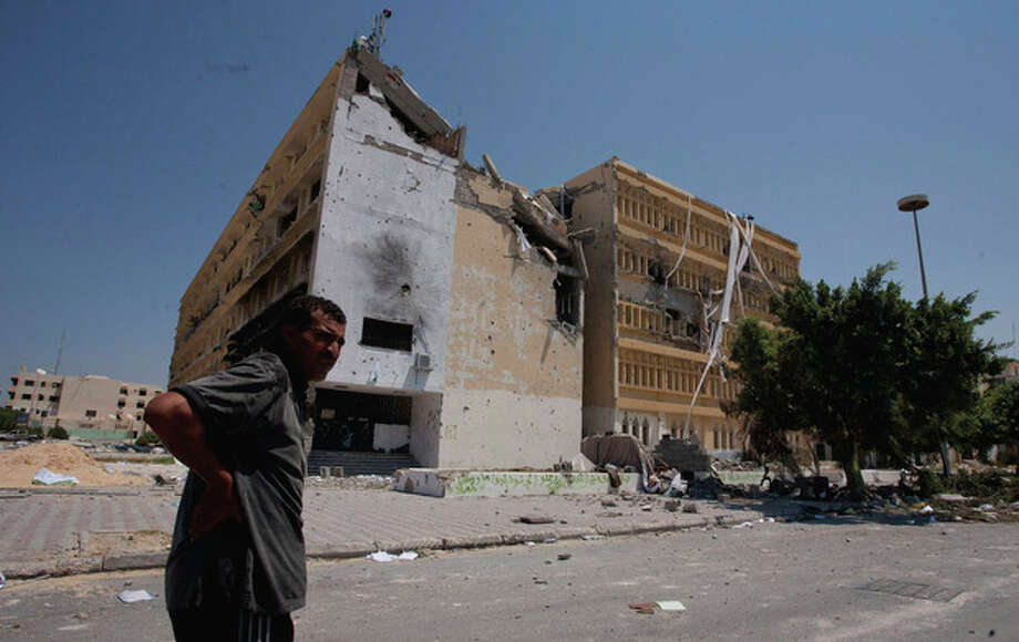 A Libyan man looks on in front of the partially destroyed building at the central square in Zawiya, LIbya, Saturday, Aug. 20, 2011. Libyan rebels expelled government forces from the strategic western city of Zawiya on Saturday, a major victory for the opposition in their march on Moammar Kadafi's stronghold of Tripoli. (AP Photo/Giulio Petrocco) / AP