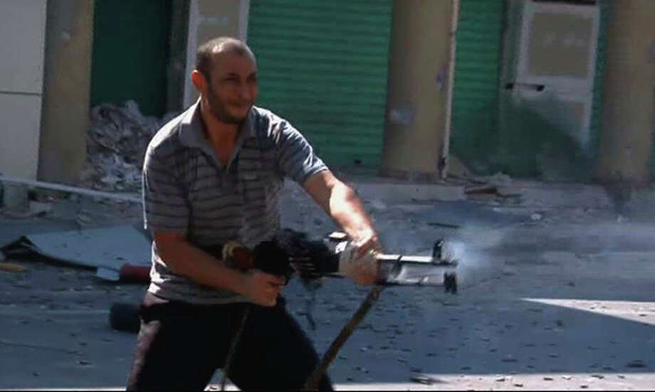 In this image from video a rebel fighter fires an automatic weapon on a street in Zawiya, Libya Friday Aug.19 2011 as they battled for control of the strategic central square in the coastal town against forces loyal to Moammar Gadhafi. Rebel forces were reported to have expelled government forces from Zawiya, a coastal city just 30 miles (50 kilometers) west of Tripoli, on Saturday Aug. 20. They also claim to have captured two more towns - Zlitan in the west and Brega in the east. The momentum in the six-month-old Libyan civil war now appears to have firmly swung in the rebels favor after months of near deadlock. (AP Photo/Sky via APTN) / Sky via APTN