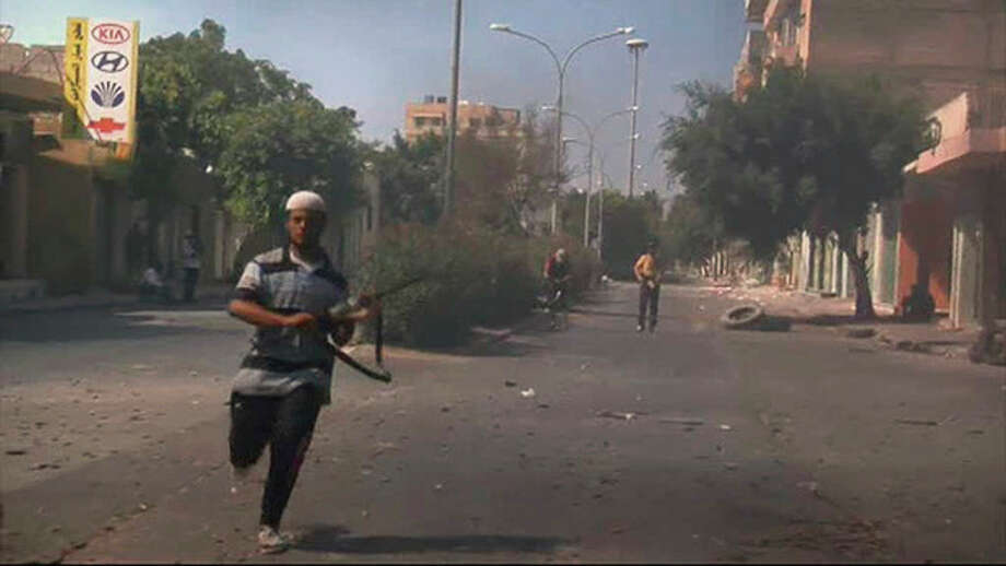 In this image from video a rebel fighter runs to cover on a street in Zawiya, Libya Friday Aug.19 2011 as they battled for control of the strategic central square against forces loyal to Moammar Gadhafi. Rebel forces were reported to have expelled government forces from Zawiya, a coastal city just 30 miles (50 kilometers) west of Tripoli, on Saturday Aug. 20. They also claim to have captured two more towns - Zlitan in the west and Brega in the east. The momentum in the six-month-old Libyan civil war now appears to have firmly swung in the rebels favor after months of near deadlock. (AP Photo/Sky via APTN) / Sky via APTN