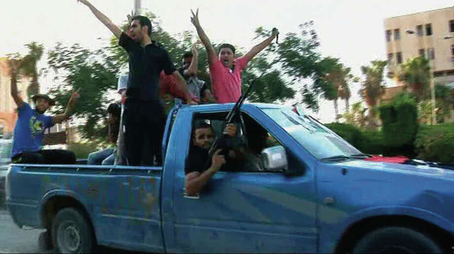 In this image from video rebel fighters celebrate victory on a street in Zawiya, Libya Friday Aug.19 2011 after they battled for control of the strategic central square against forces loyal to Moammar Gadhafi. Rebel forces were reported to have expelled government forces from Zawiya, a coastal city just 30 miles (50 kilometers) west of Tripoli, on Saturday Aug. 20. They also claim to have captured two more towns - Zlitan in the west and Brega in the east. The momentum in the six-month-old Libyan civil war now appears to have firmly swung in the rebels favor after months of near deadlock. (AP Photo/Sky via APTN) / Sky via APTN