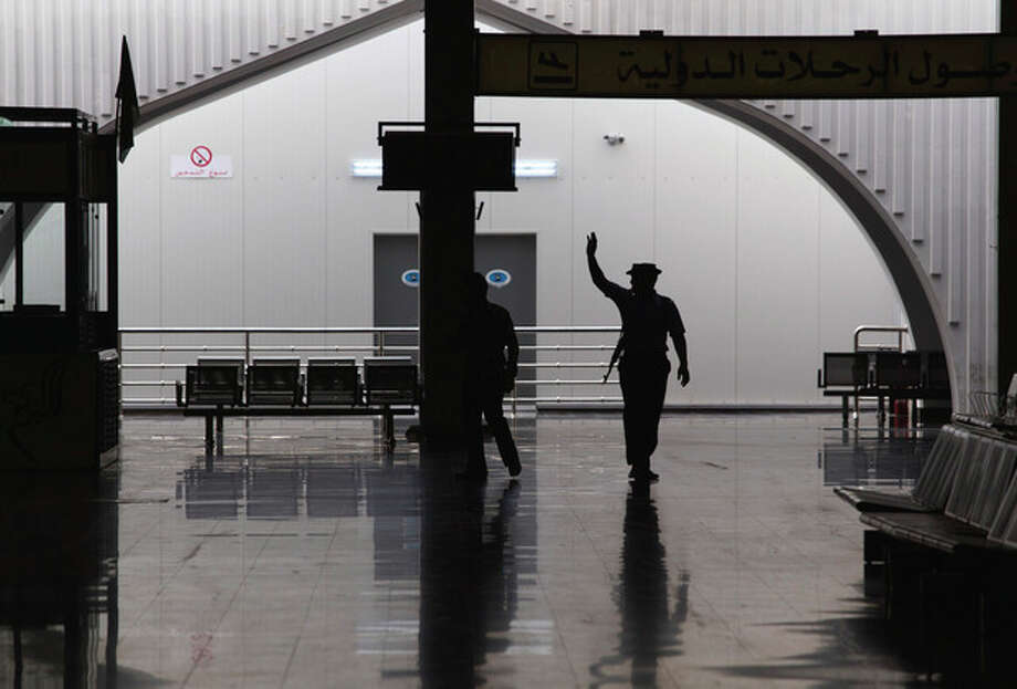 In this photo taken on a government-organized tour a guard waves to fellow officers in the main lobby of the international airport in Tripoli, Libya, Saturday, Aug. 20, 2011. The airport is in control of the government and no apparent sign of armed clashes was seen after a night of intense rumors on social networks that a rebel military operation had taken control of the capital city airport. (AP Photo/Dario Lopez-Mills) / AP