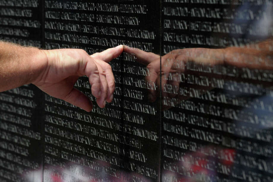 A visitor to the Vietnam Veteran's Memorial touches the name of a fallen soldier etched on the wall of the memorial in Washington, Friday, May 25, 2012. On Monday, the Vietnam Veterans Memorial Wall will begin the national commemoration of the Vietnam War's 50th anniversary. (AP Photo/Susan Walsh) / AP