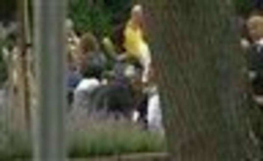 In this image from TV, Norway's Prime Minister Jens Stoltenberg, obscured behind tree at centre, bends down to comfort unidentified people outside a hotel where survivors are being reunited with family members in Sundvollen, Norway, Saturday, July 23, 2011. A Norwegian dressed as a police officer gunned down at least 84 people at an island youth retreat before being arrested, police said Saturday. Investigators are still searching the surrounding waters, where people tried to flee from the attack, which followed an explosion in nearby Oslo city centre. (AP Photo) TV OUT / APTN