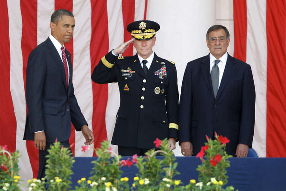 President Barack Obama arrives on stage at the Memorial Day Observance at the Memorial Amphitheater at Arlington National Cemetery, Monday, May 28, 2012. At center is Chairman of the Joint Chiefs of Staff Gen. Martin Dempsey and Defense Secretary Leon Panetta is at right. (AP Photo/Charles Dharapak) / AP