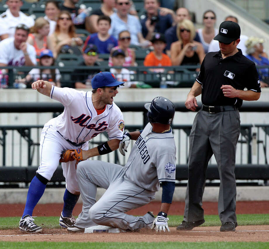 New York Mets third baseman David Wright, left, reacts as San Diego Padres' Jesus Guzman, center, is caught trying to steal third while umpire Chris Guccione, right, looks on during the seventh inning of the baseball game on Sunday, May 27, 2012, at Citi Field in New York. (AP Photo/Seth Wenig). / AP