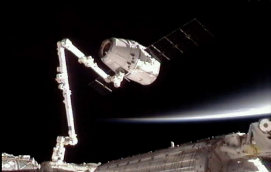 This image provided by NASA-TV shows the SpaceX Dragon commercial cargo craft, top, after Dragon was grappled by the Canadarm2 robotic arm and connected to the International Space Station, Friday, May 25, 2012. Dragon is scheduled to spend about a week docked with the station before returning to Earth on May 31 for retrieval. (AP Photo/NASA) / NASA