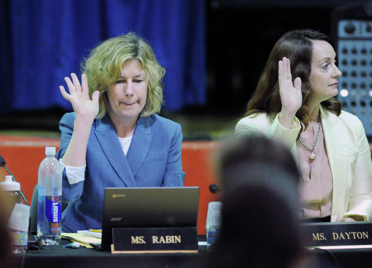 Greenwich Board of Education members, Lauren Rabin, left, and Jennifer Dayton, right, vote at the start of the final meeting of the school year that was held in the New Lebanon School gym in the Byram section of Greenwich on Tuesday night. June 14, 2016.